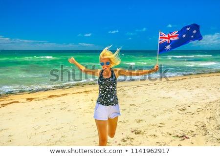 Woman waving Australian flag on beach Stock photo © lovleah