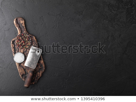 Vintage meat knife and fork with stone chopping board and black table background. Butcher utensils.  Stock photo © DenisMArt