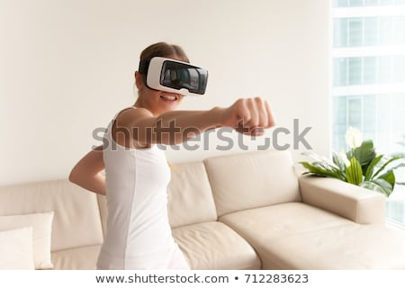 young woman watching videos or playing with vr glasses on head stock photo © dash