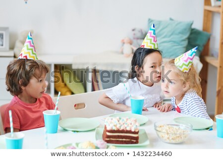 One of cute girls in birthday caps whispering something to her friend Stock photo © pressmaster