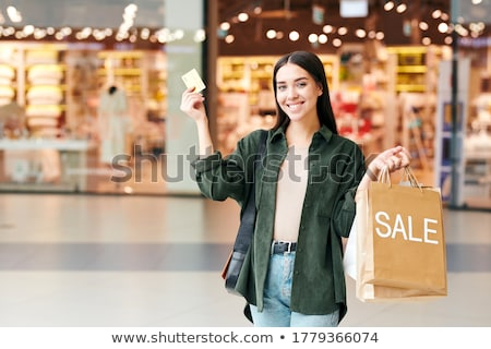 Young casual shopaholic with paperbags showing you credit card Stock photo © pressmaster