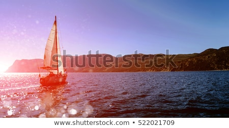 white yacht with sail set goes along the island on a hot day blue sea blue sky crimea on board a stock photo © elenabatkova
