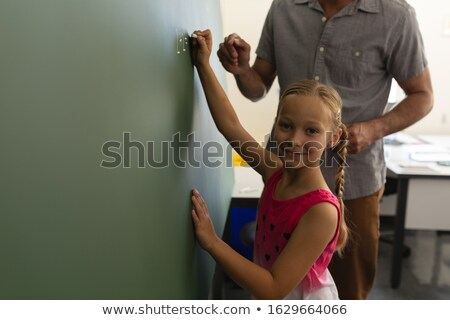 Schoolgirl with math teacher looking at camera and writing on chalk board in classroom of elementary Stock photo © wavebreak_media