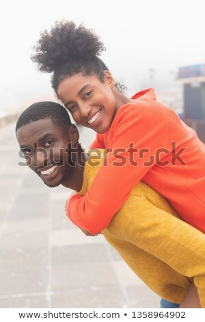 Portrait of handsome African American man carrying Mixed-race woman piggyback at pavement. They are  Stock photo © wavebreak_media