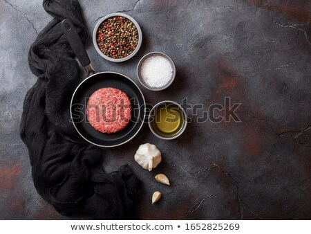 Raw minced homemade grill beef burger in frying pan. Top view and space for text. With pepper salt a Stock photo © DenisMArt