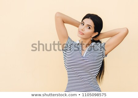 Portrait of pretty female with dark hair, makes pony tail, dressed in casual striped t shirt, looks  Stock photo © vkstudio