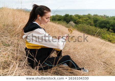 Photo of nice brunette woman using earpods and smartwatch while sitting Stock photo © deandrobot
