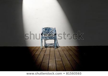 Spotlight on single iron chair on wooden floor Stock photo © Ansonstock