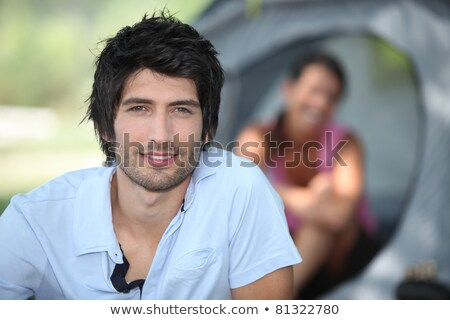 Young man camping with his girlfriend and tent out of focus in the background Stock photo © photography33