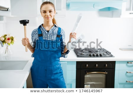 Stock photo: Woman holding a pipe wrench