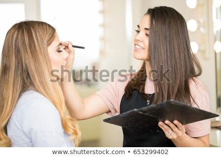 Make-up artist putting some eye-shadow on a beautiful woman in a studio Stock photo © wavebreak_media