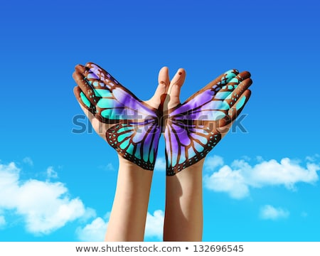 lovely woman with a butterfly over blue sky stock photo © nejron