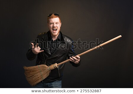 man in leather jacket playing on a broom stock photo © feelphotoart