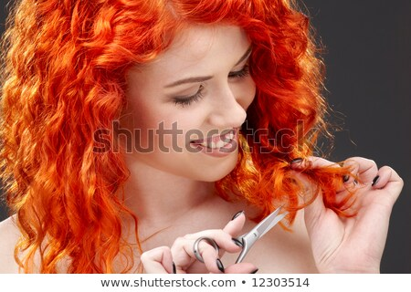 Cheerful woman cutting splitting ends of long hair with scissors  Stock photo © deandrobot