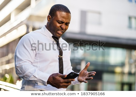 angry businessman using smartphone stock photo © deandrobot