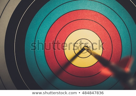 Stock photo: Archer aiming with bow and arrow at the target.