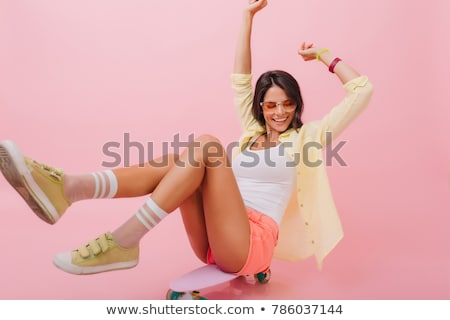 Young woman listening music with headphones while sitting on skateboard Stock photo © deandrobot