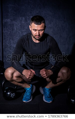 Stock photo: Portrait of male trainer standing by athlete lifting kettlebells