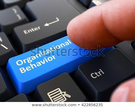 Stock photo: Finger Presses Blue Keyboard Button Organizational Behavior.