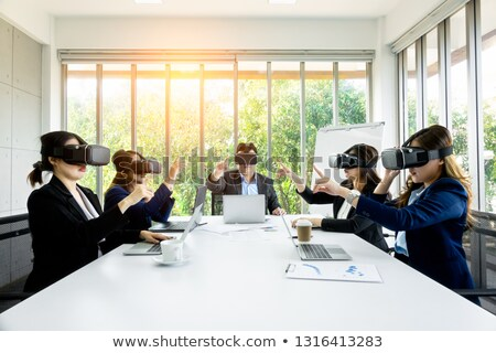 Stok fotoğraf: Businessmen Using Virtual Reality Headset In Conference Room