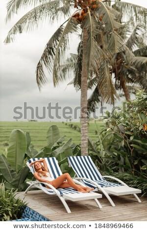 Beautiful woman in white bikini sitting by pool side Stock photo © wavebreak_media