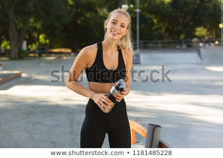 beautiful amazing happy young sports woman holding water outdoors stock photo © deandrobot