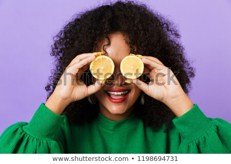 happy pretty african woman isolated over violet background holding lemons stock photo © deandrobot