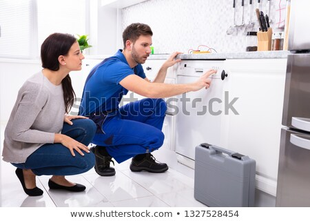 serviceman pressing button of dishwasher in kitchen stock photo © andreypopov