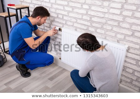 Woman Looking At Plumber Installing Radiator With Screwdriver Stock photo © AndreyPopov