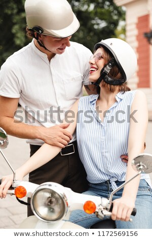 Vertical image of cheerful young couple in crash helmets posing Stock photo © deandrobot