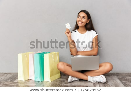 woman sitting near shopping bags isolated over grey wall background holding credit card using laptop stock photo © deandrobot