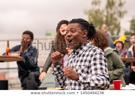 Young male football fan and his friends expressing excitement during match Stock photo © pressmaster