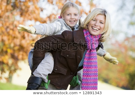 Mother giving daughter piggyback ride in autumn woodland Stock photo © Lopolo
