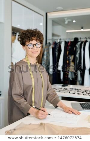 Jóvenes exitoso femenino sastre mirando papel Foto stock © pressmaster