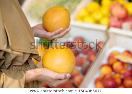 hands of young female buyer holding fresh ripe yellow grapefruits stock photo © pressmaster