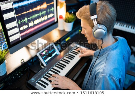 Contemporary musician in headphones recording new music and songs in studio Stock photo © pressmaster