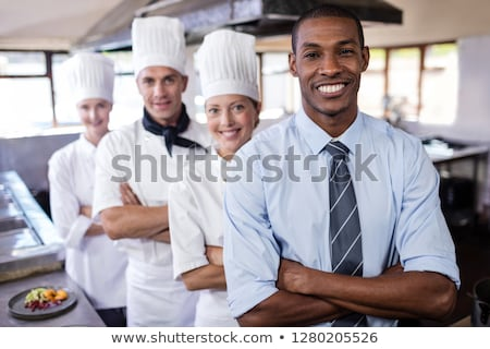 Group of chefs and manager standing with arms crossed in kitchen at hotel Stock photo © wavebreak_media