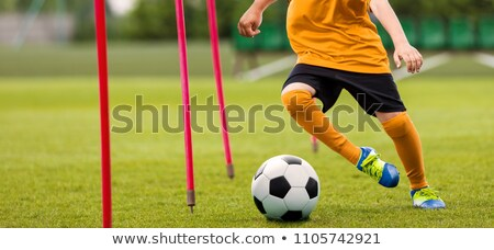 yellow soccer training cones on grass field youth football players on training in the background stock photo © matimix