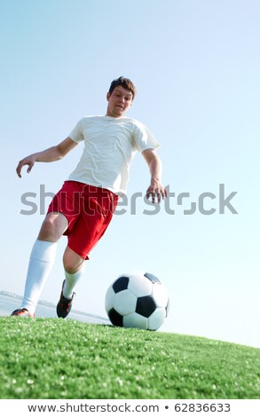 Active young football player in blue sports uniform going to kick soccer ball Stock photo © pressmaster