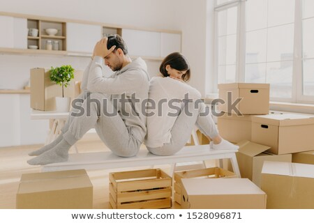 Unhappy young married woman and man have to leave house, move in other place, sit back to each other Stock photo © vkstudio