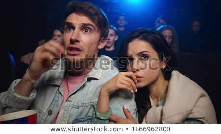 Young scared dates with box of popcorn watching horror movie at leisure Stock photo © pressmaster