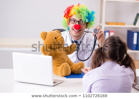Funny pediatrician with little girl at regular check-up Stock photo © Elnur