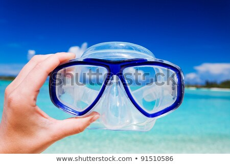 hand holding diving goggles on sea beach stock photo © ia_64