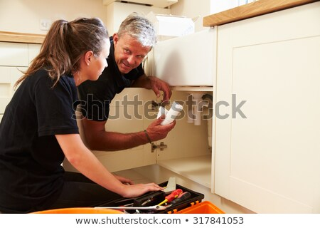 Young female apprentice plumbing a sink Stock photo © photography33