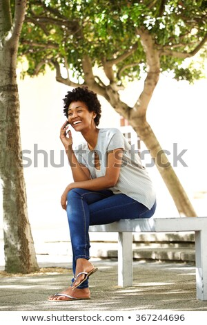 Full length portrait of confident young woman sitting, outdoors Stock photo © Victoria_Andreas