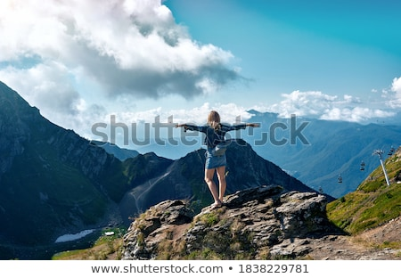 Young woman standing on cliff's edge Stock photo © gladcov