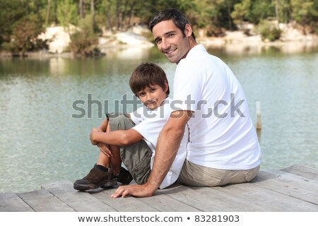 a father and his son seated on a pontoon faces a lake Stock photo © photography33