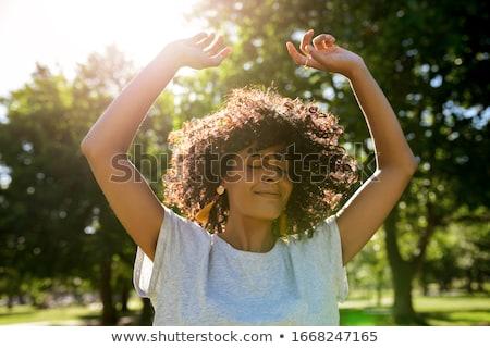 Jeune femme permanent parc ensoleillée après-midi yeux fermés Photo stock © epstock