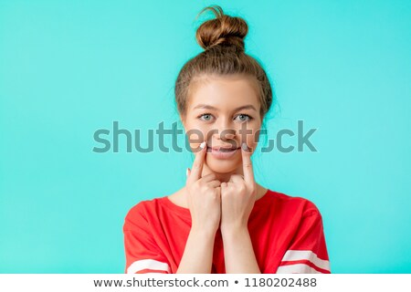 Smiling girl put her fingers to head Stock photo © cherezoff