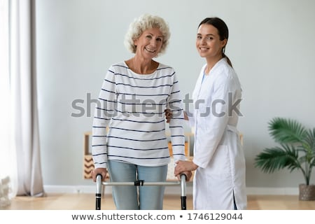 Happy elderly woman using a walking aid Stock photo © belahoche
